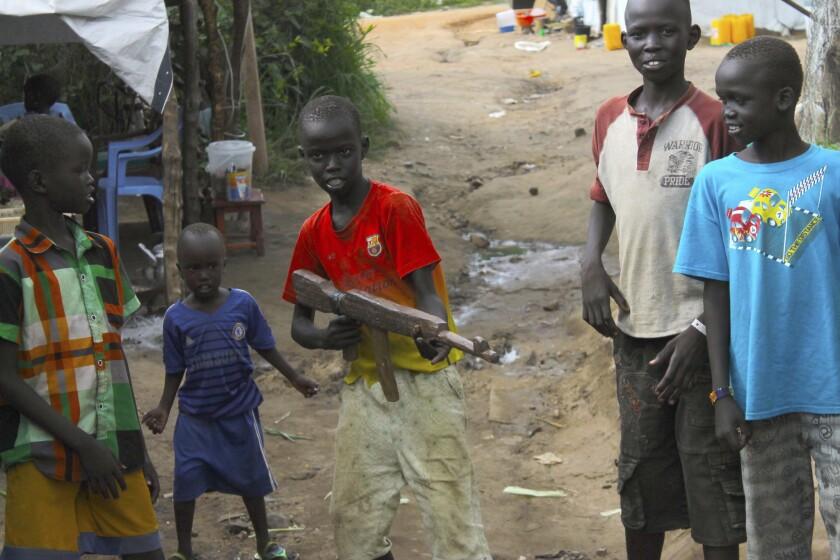 ARCHIVO - Esta foto de archivo tomada el lunes 25 de julio del 2016 muestra a un grupo de niños en la zona para protección de civiles de la ONU, en Juba, Sudan del Sur, jugando, uno de ellos con un arma de juguete. El presidente Barack Obama ha emitido exenciones que mantienen en efecto millones de dólares en ayuda militar al atribulado Sudan del Sur y otros seis países donde se han usados a niños soldados. (AP Foto/Justin Lynch/Archivo)