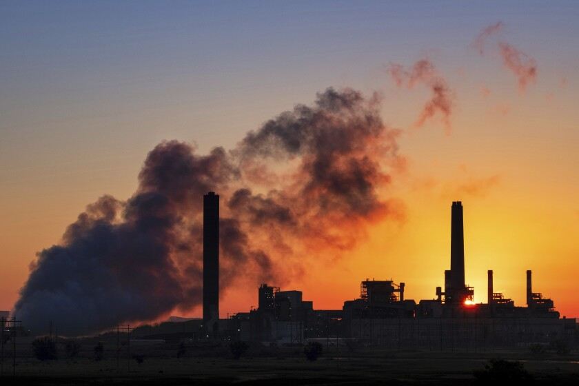 The Dave Johnston coal-fired power plant is silhouetted against the morning sun in Glenrock, Wyo.