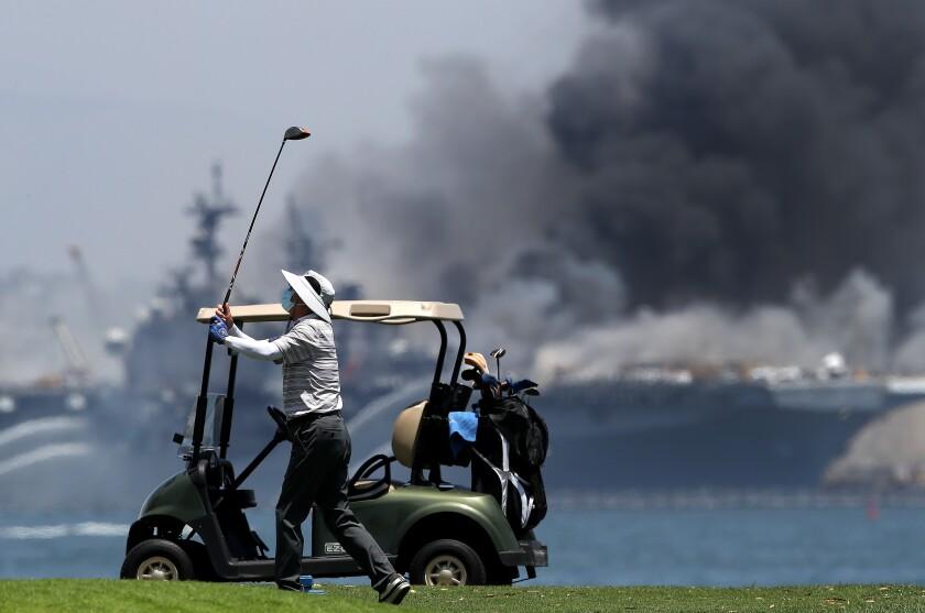 A golfer plays on as a fire burns on the amphibious assault ship USS Bonhomme Richard