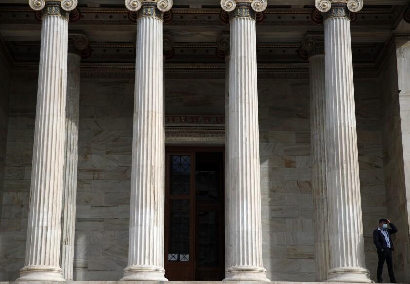 Un hombre con mascarilla está en la entrada de la Academia Atenas en la capital griega, martes 24 de noviembre de 2020. (AP Foto/Thanassis Stavrakis)