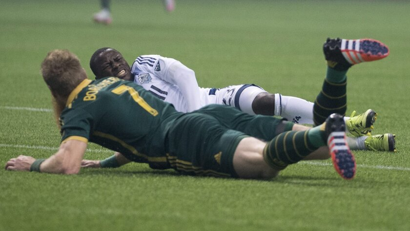 Vancouver Whitecaps FC Kekuta Manneh (23) reacts after being hit by Portland Timbers FC Nat Borchers (7) during the first half of MLS soccer action in Vancouver, British Columbia, Canada, Sunday, Nov. 8, 2015. (Jonathan Hayward/The Canadian Press via AP)