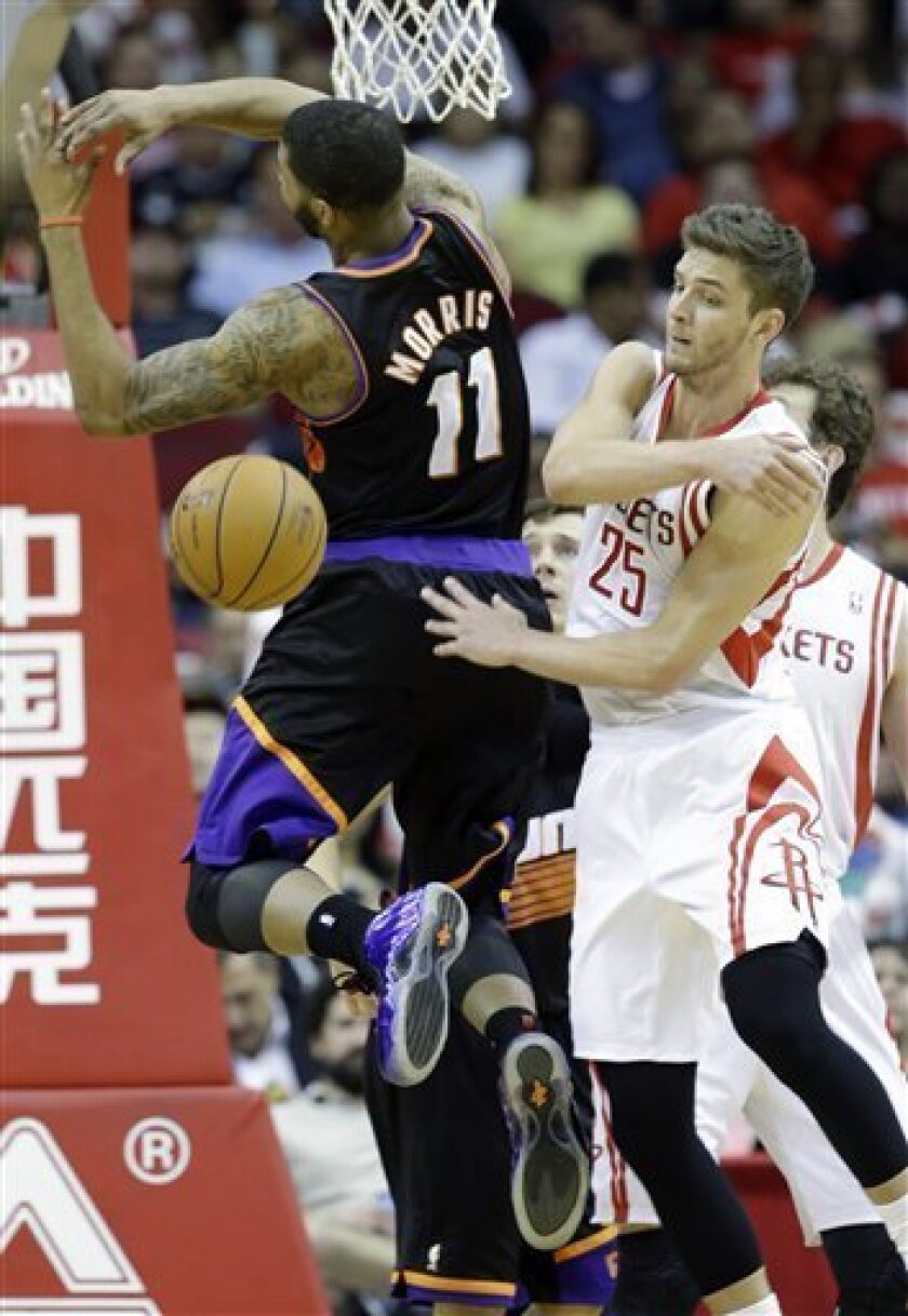 Houston Rockets' Chandler Parsons (25) knocks the ball away from Phoenix Suns' Markieff Morris (11) during the third quarter of an NBA basketball game Wednesday, March 13, 2013, in Houston. (AP Photo/David J. Phillip)