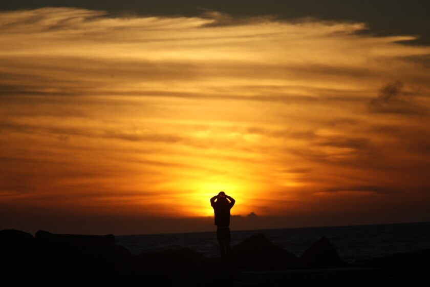Nolan Kopp, 23, of Glendale watches the sun set Thursday over Venice Beach, after rain drenched much of Southern California.
