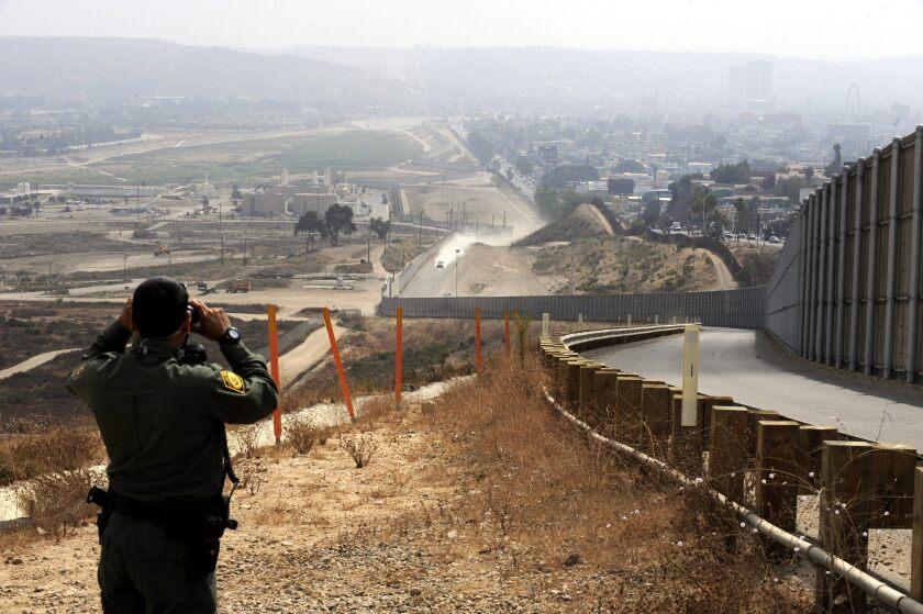 Un oficial de la Patrulla Estadounidense de Frontera observa a través de sus binoculares hacia Tijuana