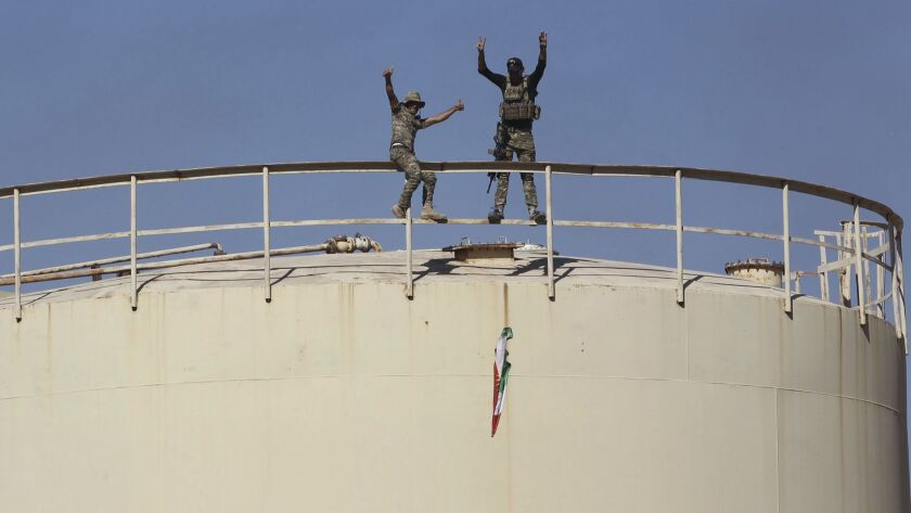 Iraqi government forces remove a Kurdish flag from the Bai Hasan oil field west of Kirkuk on Oct. 17.