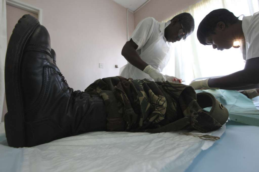 The health benefits of circumcision outweigh the risks, the CDC says in new draft guidelines issued Dec. 2. Much of the evidence is based on studies in Africa. Above, a doctor and nurse perform a circumcision on a soldier in Harare, Zimbabwe.