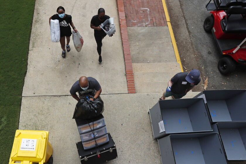 Varias personas transportan materiales el viernes 31 de julio de 2020 al comenzar a llegar los estudiantes
