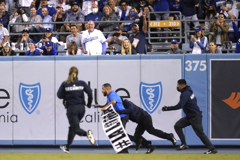 """A protester is tackled after running onto the field at Dodger Stadium with a banner reading """"#LaLoma."""""""