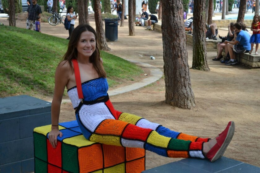 Marcy Kraft, who yarn-bombed herself, sits atop one of 30 cubes she and her crocheting cohorts decorated in Children's Park downtown.