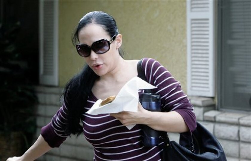 FILE - In this March 11, 2009 file photo, Nadya Suleman, the mother of octuplets, leaves her home in Whittier, Calif. People magazine reported Sunday May 31, 2009, on its Web site that Suleman reportedly signed a deal to star in a reality television series to be filmed by a British production compa