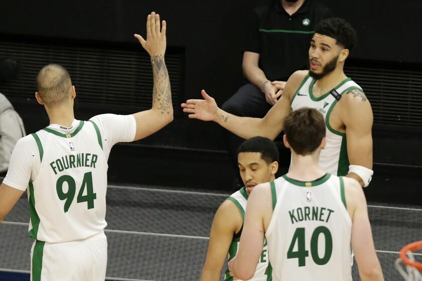 El alero de los Celtics de Boston Jayson Tatum felicita a Evan Fournier, junto a Luke Kornet y Tremont Waters en el encuentro ante los Timberwolves de Minnesota del sábado 15 de mayo del 2021.. (AP Photo/Andy Clayton-King)