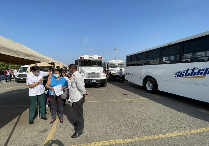 People are lined up outside next to buses. A health worker is giving one woman a shot.