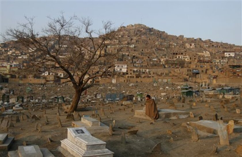Muhammed Yasin, 35, sits in a cemetery in Kabul, Afghanistan, Wednesday, Jan, 11, 2012. (AP Photo/Ahmad Jamshid)