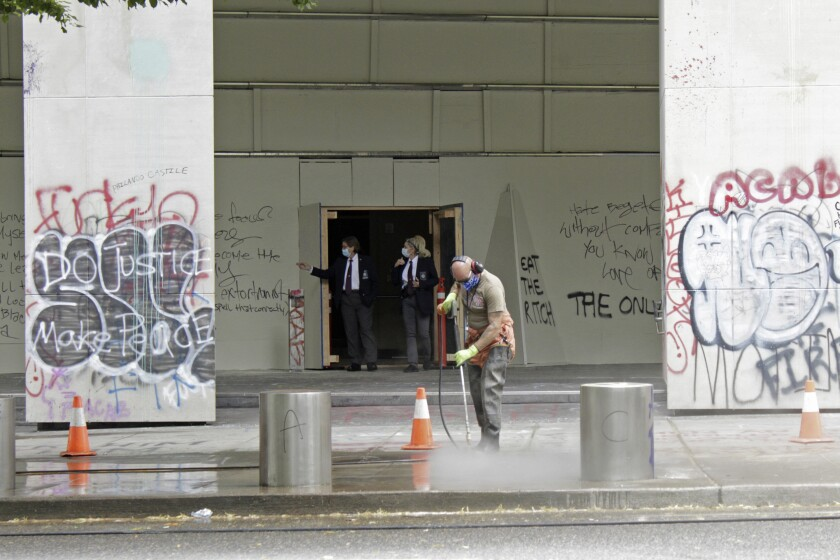 FILE - In this July 8, 2020, file photo, a worker washes graffiti off the sidewalk in front of the Mark O. Hatfield Federal Courthouse in downtown Portland, Ore., as two agents with the U.S. Marshals Service emerge from the boarded-up main entrance to examine the damage. Oregon's largest city is in crisis as violent protests have wracked downtown for weeks. (AP Photo/Gillian Flaccus, File)