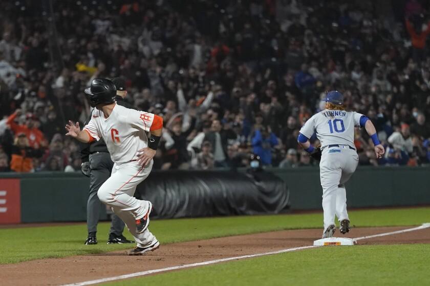 Buster Posey, izquierda, de los Gigantes de San Francisco, corre al plato para anotar una carrera mientras el tercera base Justin Turner (10) de los Dodgers de Los Ángeles, va por la pelota luego de un error de tiro del primera base Cody Bellinger en el octavo inning del partido del martes 27 de julio de 2021, en San Francisco. (AP Foto/Jeff Chiu)
