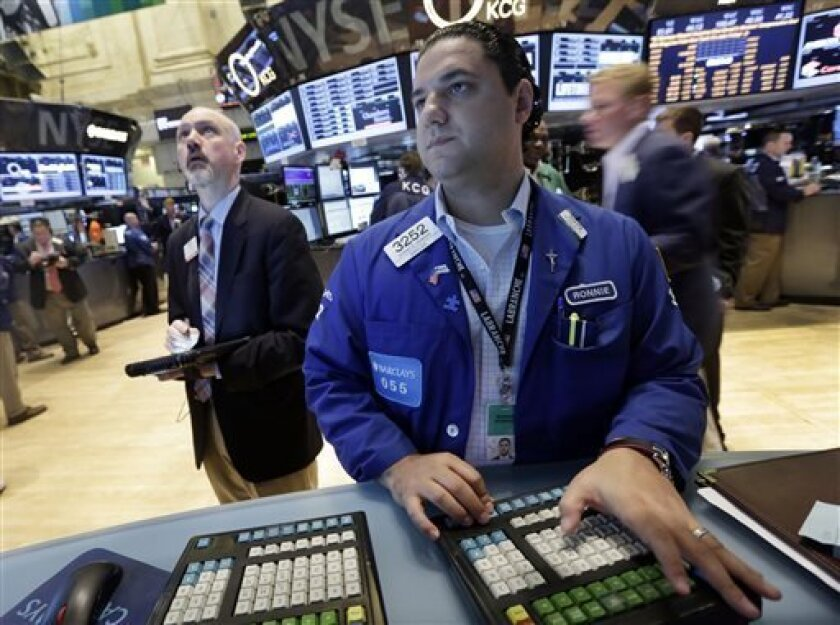 Specialist Ronnie Howard, center, work at his post on the floor of the New York Stock Exchange Friday, July 5, 2013. Robust hiring in the U.S. is boosting the stock market in early trading. (AP Photo/Richard Drew)