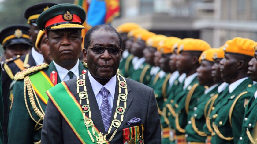 FILE- In this Tuesday, Oct. 6, 2009 file photo, Zimbabwe's President Robert Mugabe inspects the guar