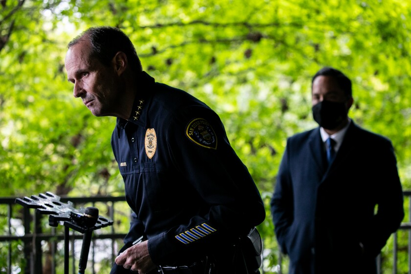 A man in a police uniform leans over a microphone as a man in a suit watches.