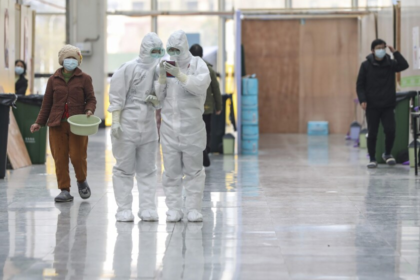 In this Friday, Feb. 21, 2020, photo, nurses in protective suits look at a smartphone at a temporary hospital at Tazihu Gymnasium in Wuhan in central China's Hubei province.