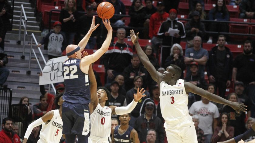 SAN DIEGO, February 9, 2019 | The Aztecs' Aguek Arop, right, and Devin Watson try to block as Utah S