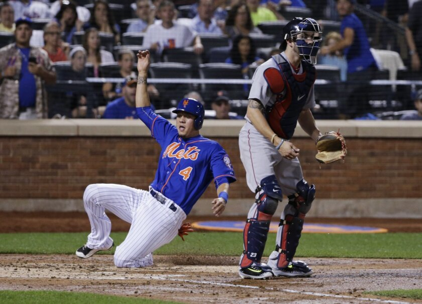New York Mets' Wilmer Flores (4) slides past Boston Red Sox catcher Blake Swihart to score on a single by Travis d'Arnaud during the fourth inning of a baseball game Friday, Aug. 28, 2015, in New York. (AP Photo/Frank Franklin II)
