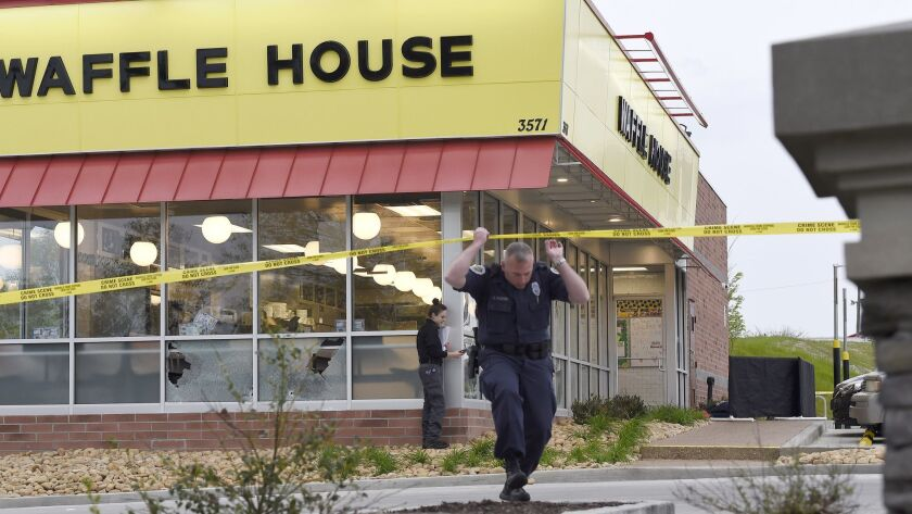 Law enforcement officials work the scene of a fatal shooting at a Waffle House in the Antioch neighb