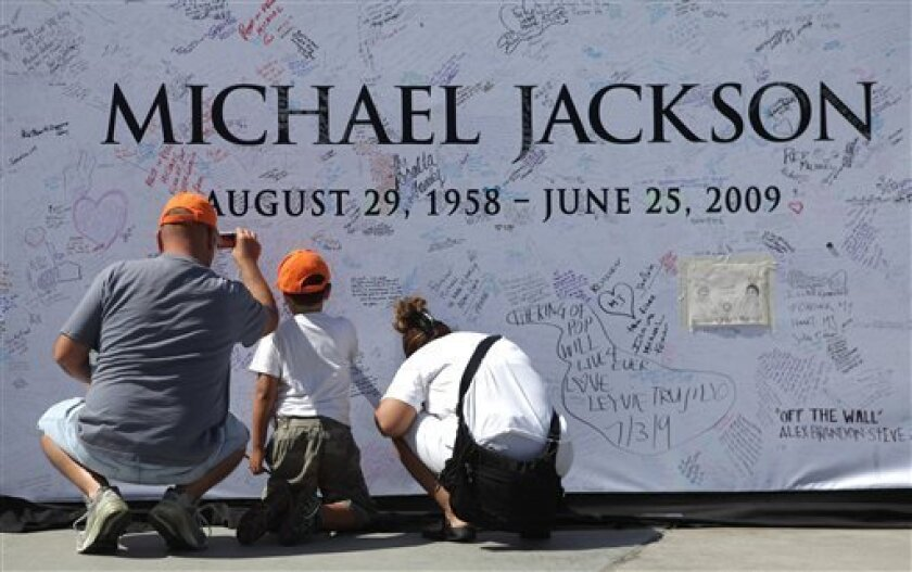 Michael Navarro, left, Michael Navarro, Jr., 7, center, and Gina Rodriguez, all from Los Angeles, sign and photograph a large poster at the Staples Center in Los Angeles, Saturday, July 4, 2009, which will be the site for the late pop star Michael Jackson's memorial service taking place Tuesday, July 7, 2009. (AP Photo/Carolyn Kaster)