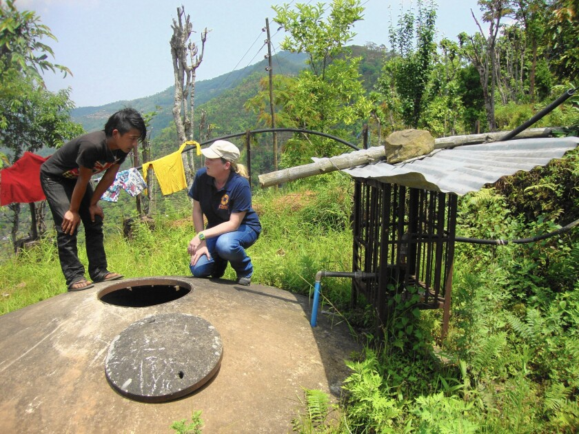 Bikash Ranamayar, 20, a local student, helps Tess Gough, right, a sanitation expert with the Atlanta-based non-profit CARE, inspect a water tank in Paslang, Nepal, about 140 miles west of the capital.