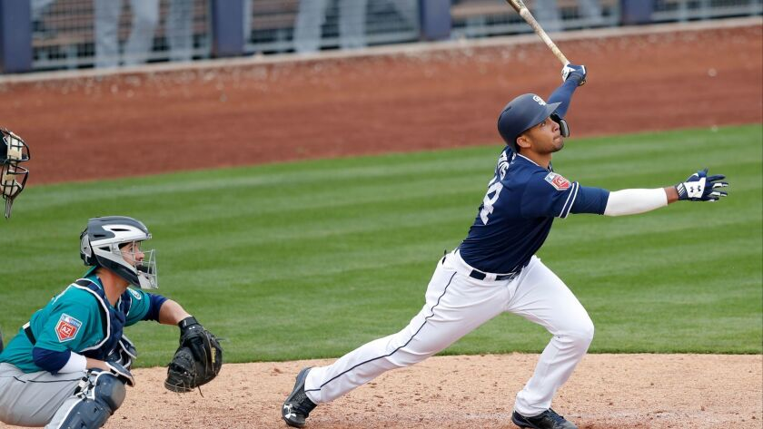 San Diego Padres' Fernando Tatis watches a home run in front of Seattle Mariners catcher Tuffy Gosewisch during the eighth inning of a spring training baseball game Friday.