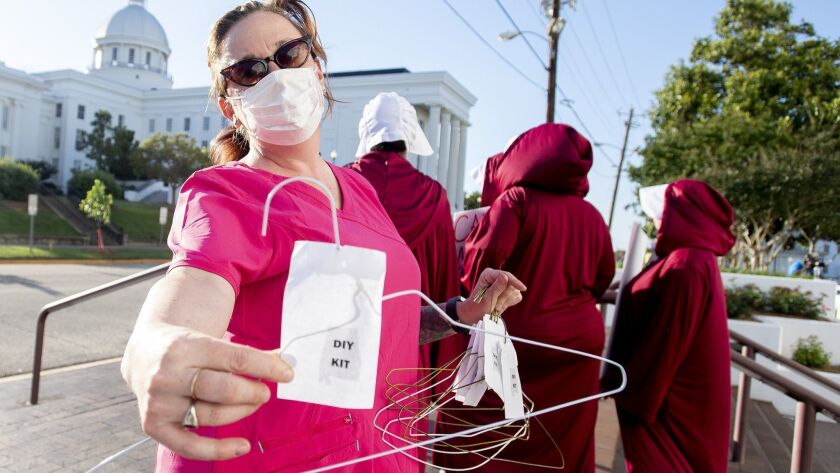 Laura Stiller hands out coat hangers as she talks about illegal abortions during a rally against HB3