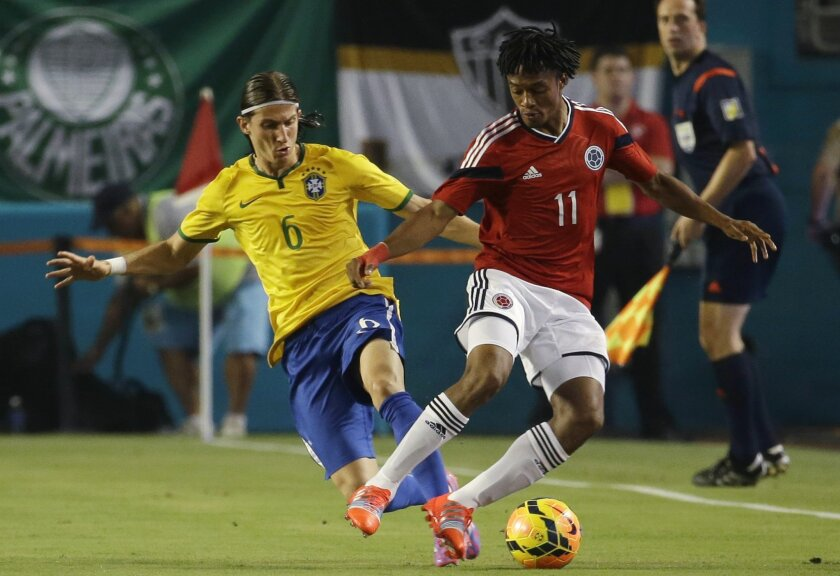 Brazil's Filipe Luis (6) goes for the ball with Colombia's Juan Guillermo Cuadrado (11) during the first half of an international friendly soccer match, Friday, Sept. 5, 2014, in Miami Gardens, Fla. (AP Photo/Lynne Sladky)