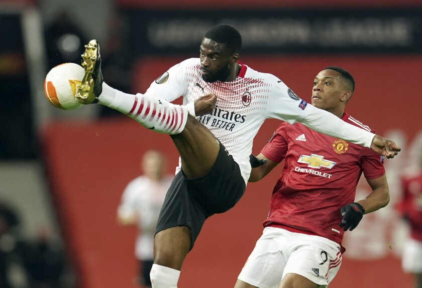 FILE - In this Thursday, March 11, 2021 file photo, AC Milan's Fikayo Tomori, left, and Manchester United's Anthony Martial challenge for the ball during their Europa League round of 16 first leg soccer match at Old Trafford in Manchester, England. AC Milan has exercised its option to sign Fikayo Tomori from Chelsea after the defender's loan spell with the Italian club in the second half of the season, it was announced Friday, June 18. The Serie A club paid a reported fee of at least $33 million for the 23-year-old Tomori. (AP Photo/Dave Thompson)