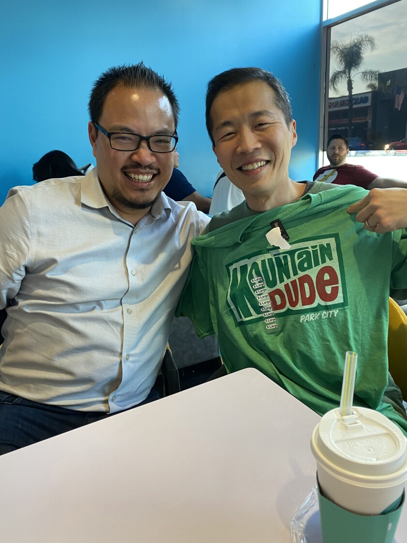 L.A. Times critic Justin Chang and Lee Isaac Chung at a table. Chung holds up a Mountain Dude T-shirt.