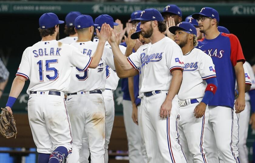 The Texas Rangers celebrate a win over the Chicago White Sox in a baseball game, Saturday, Sept. 18, 2021, in Arlington, Texas. (AP Photo/Brandon Wade)