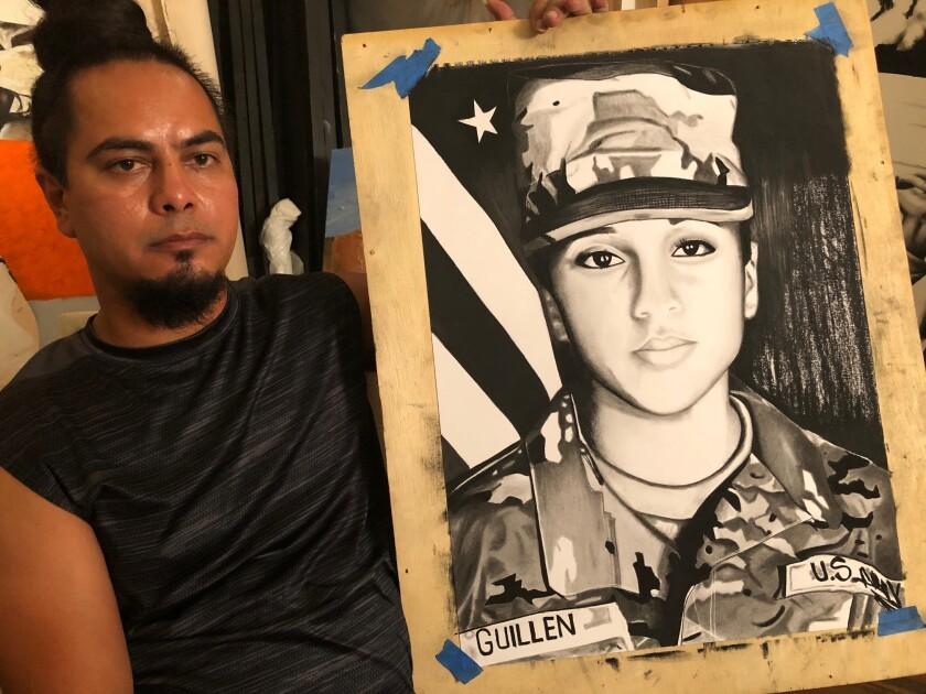Enrique Espinoza posa junto a la última obra de arte que terminó el jueves anterior.