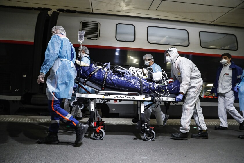 Medical staff wheel a patient infected with COVID-19 through the Gare d'Austerlitz train station in Paris on Wednesday. That patient and 35 others were being sent by high-speed train to hospitals in Britany, which has been less affected by the outbreak.
