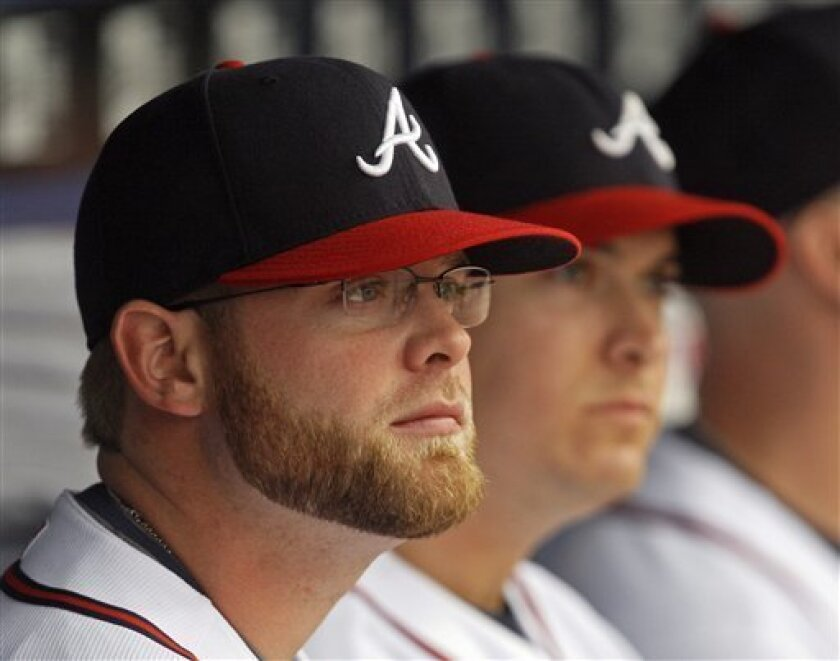 Atlanta Braves catcher Brian McCann wears his new glasses as he sits on the bench before a baseball game against the Houston Astros in Atlanta, Friday, May 1, 2009. McCann is hoping the glasses will correct a vision problem that has kept him out of the lineup. (AP Photo/John Bazemore)