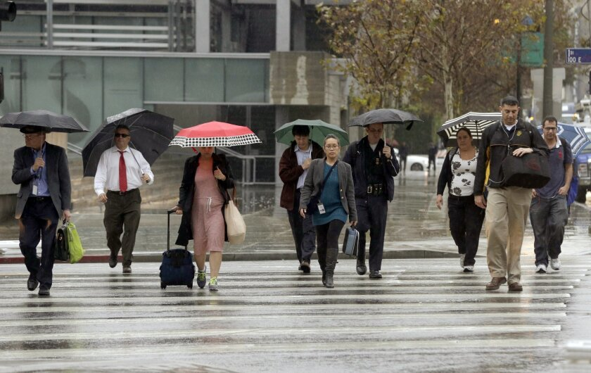 Commuters walk under a light rain downtown in Los Angeles on Wednesday, Feb. 17, 2016, as a storm system arriving in California ends days of clear skies, blazing sunshine and record-setting heat. The National Weather Service said the storm would arrive in Southern California by night, bringing gust
