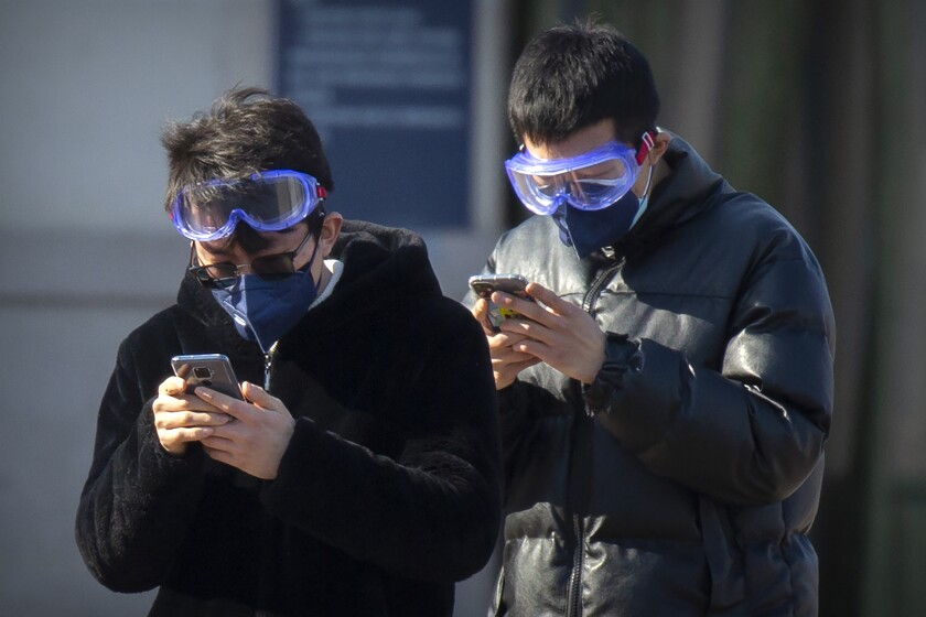 Travelers wear face masks and goggles as they use their smartphones outside the Beijing Railway Station on Saturday in Beijing.