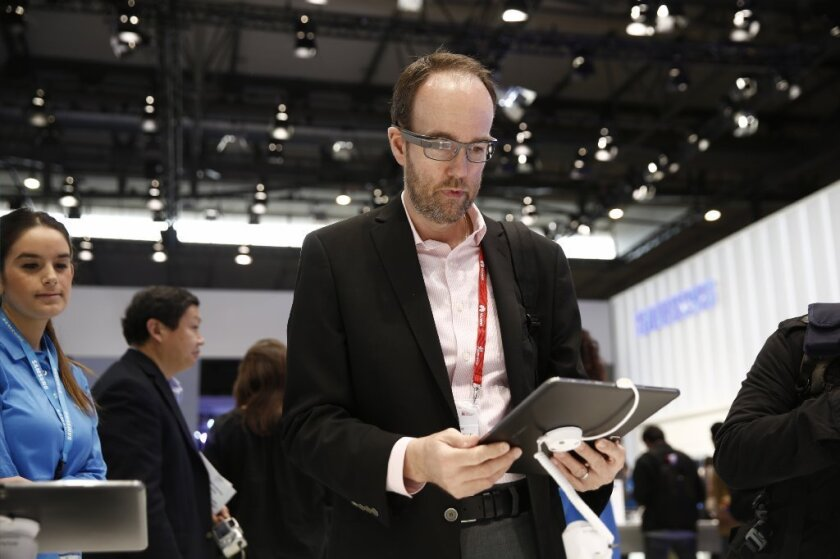 A man wears Google Glass while browsing a tablet at the Mobile World Congress trade show in Barcelona, Spain.