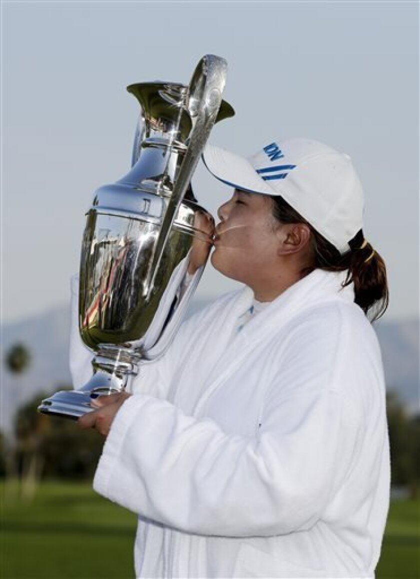 Inbee Park, of South Korea, kisses the trophy after winning the LPGA Kraft Nabisco Championship golf tournament in Rancho Mirage, Calif., Sunday, April 7, 2013. (AP Photo/Chris Carlson)