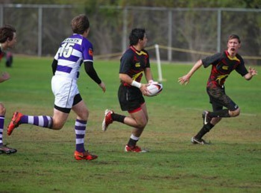 """(Left) Torrey Pines Fullback Bernardo Olivas pitches to Senior teammate Kevin Cahill in the opening minutes of a High School Rugby Match played Saturday, Dec. 15, 2012, at the """"Little Q."""" Cahill scored a few seconds after this pass, and then used his whippet-like speed from the Left Wing position t"""