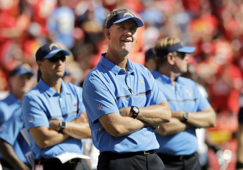Chargers coach Mike McCoy, center, and his staff watch the Kansas City Chiefs celebrate after their overtime win in Sunday's season opener.