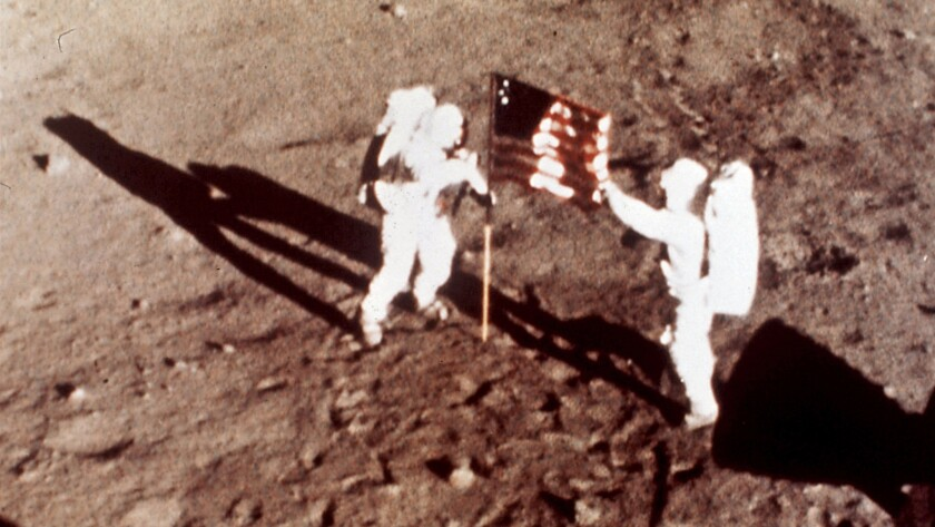 Apollo 11 astronauts Neil Armstrong and Buzz Aldrin plant the U.S. flag on the lunar surface. A new study finds astronauts who traveled to the moon are more likely to die of cardiovascular disease than those who stayed in low-Earth orbit.