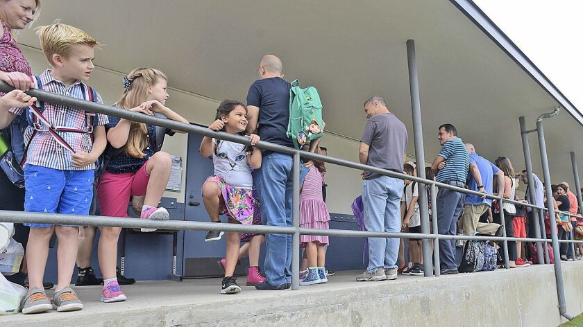 Parents and students line up outside their new classrooms as they wait for school to begin at Thomas