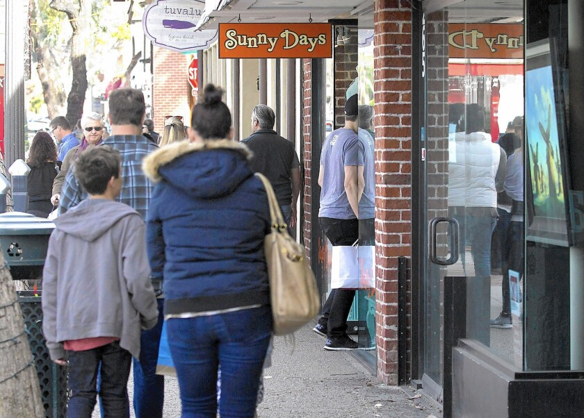 Shoppers browse along Forest Avenue the day after Christmas in downtown Laguna.