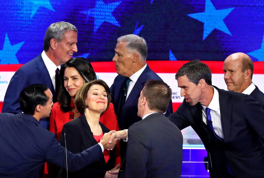Democratic presidential candidates shake hands and greet moderator Chuck Todd of NBC News, center, after the first night of the party's first primary debate last month.