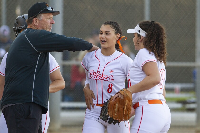 Huntington Beach's pitcher Grace Uribe gets a pat on the back from head coach Jeff Forsberg during a