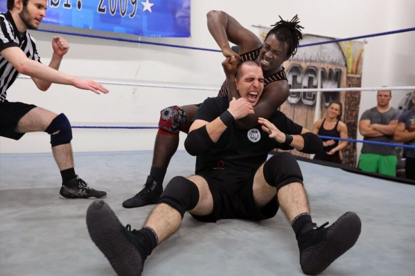 Pro wrestler Ju Dizz puts fellow grappler Hunter Freeman in a headlock as the two trained at SoCal Pro Wrestling's new San Marcos gym on Monday