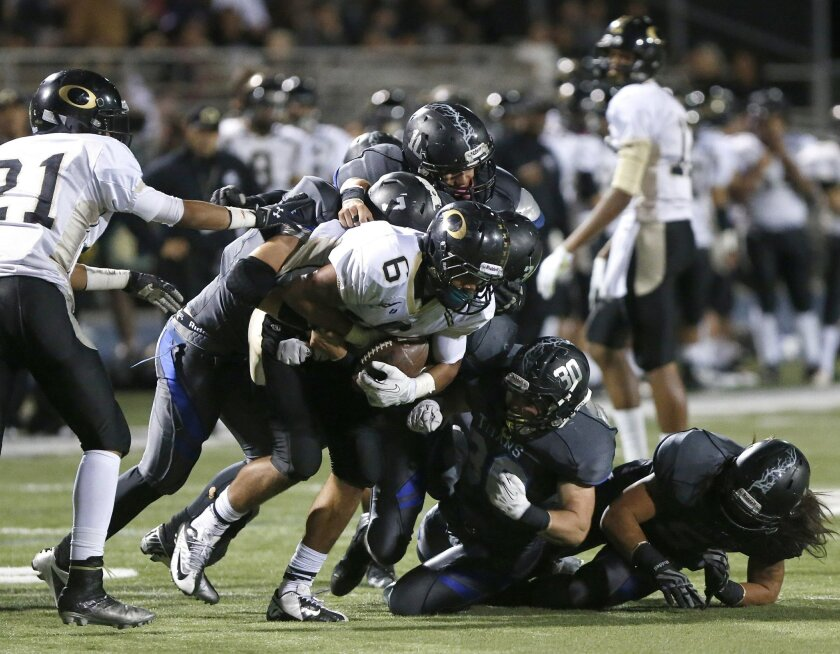 Olympian's Manny Rodriquez gets swarmed by Eastlake's defense during Eastlake High School's victory over Olympian Friday night at Eastlake.